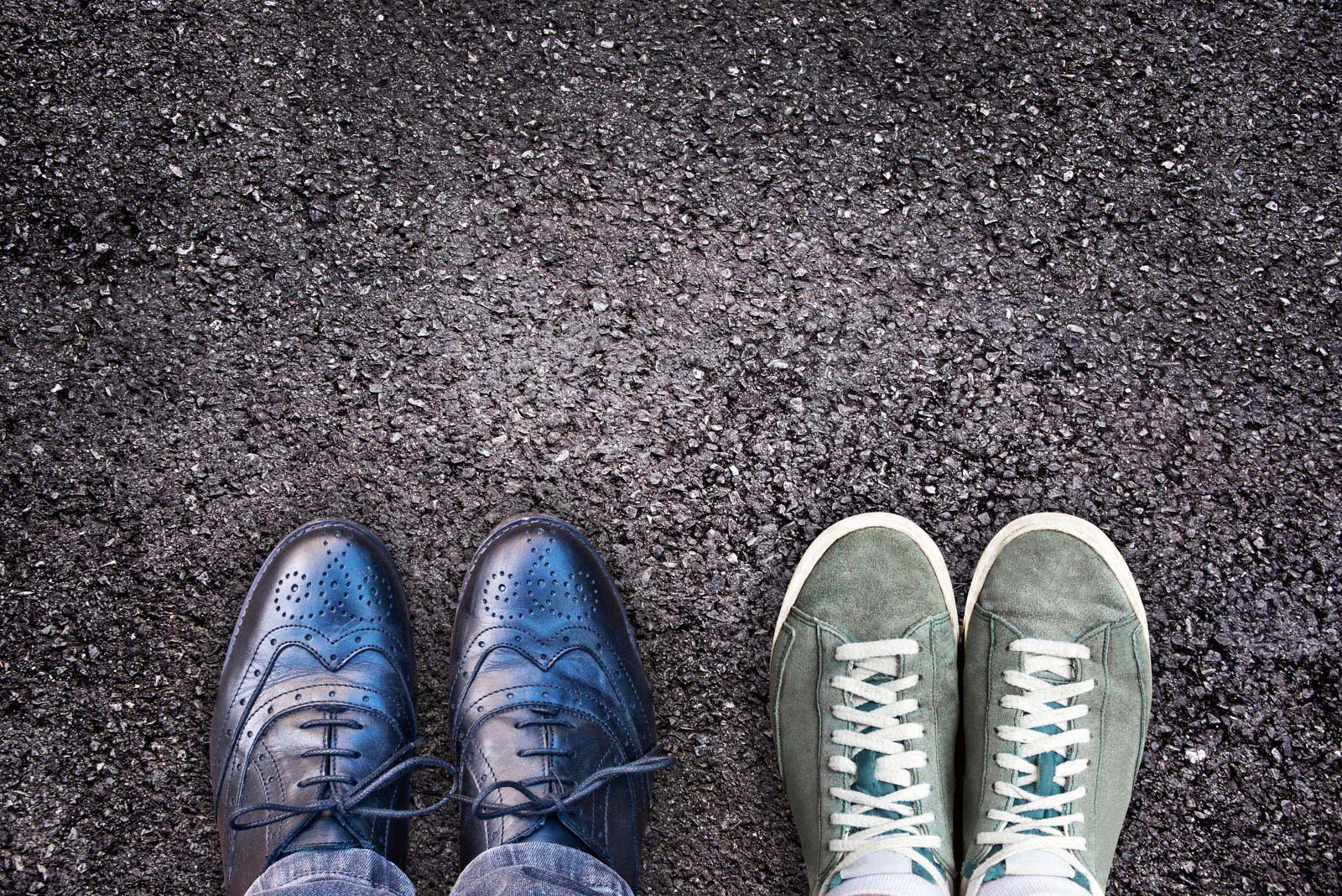 Sneakers and business shoes side by side on ground